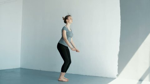 Young woman beginner gymnast trying to do the splits in a jump. Flexible girl learns to dance