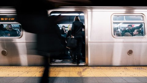 New York City, United States - Apr 4, 2019: Time-lapse of people waiting and boarding trains at subway station platform in New York city, USA. American city life, or public transportation concept