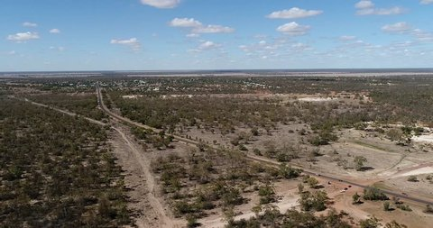 Endless flat plains of Australian outback around Lightning ridge opal mining town. Aerial hovering along single road connecting town to highway.
