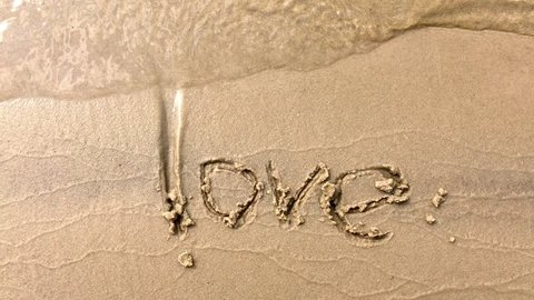 Top view of the waves that float on the sandy beach on which the word love is written.