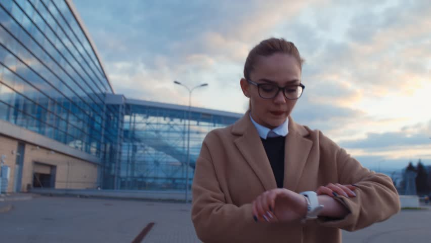 Close up view of pretty blonde businesswoman in trendy coat and glasses walking by the airport checking her wristwatch. Hurrying up, no time, rushing. Active lifestyle. Female portrait