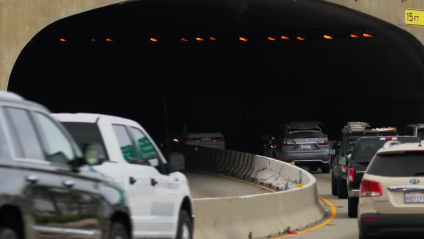 This telephoto zoom video shows busy freeway traffic going through a tunnel.