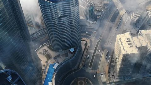 Top aerial view shot of skyscrapers in the city with fog clouds passing by - Abu Dhabi Al Reem island Sun and Sky towers