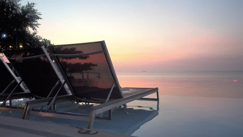 Locked-off shot of lounge chairs next infinity swimming pool, pink sunset sky and ocean background.