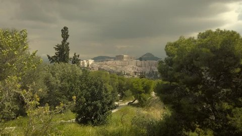 4K Tilt up Magnificent view of  Parthenon, Acropolis, Athens, Attica, Greece between forest, butterfly in shot