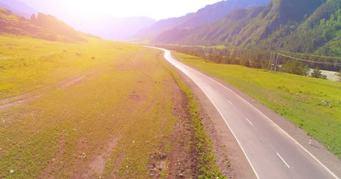 Aerial UHD 4K view. Low air flight over mountain asphalt highway road and meadow at sunny summer morning. Near green trees. Fast horizontal movement with sun rays.