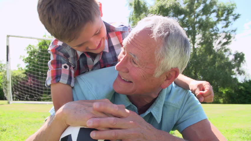 Slow motion sequence of grandson lying on grandfather's back as they play football together. Shot on Sony FS700 at frame rate of 100fps #10288901