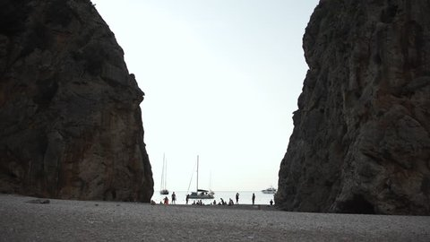 Silhouette of tourists and yachts between two cliffs in Torrent de Pareis in Sa Calobra, Mallorca, Spain