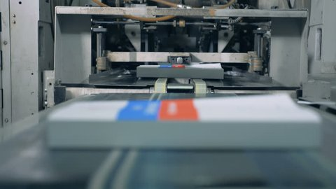 Many books moving on a conveyor in a print office, modern technology.
