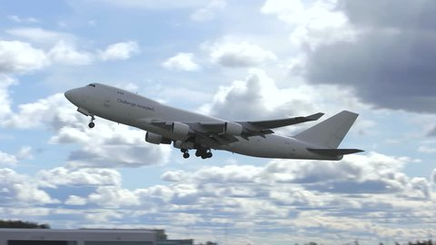 oslo airport norway - ca may 2019:  huge cargo airplane boeing 747 jumbo jet taking off runway panning left ambient sound audio recording back lit scenery