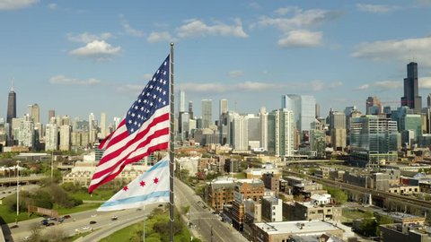 Push in past American and Chicago Flags waving in the wind towards Chicago Skyline [4K] [Aerial]