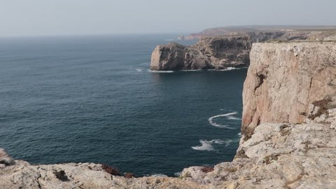 Stunning shot of Algarve coast from cliff onto the blue ocean in evening sunlight