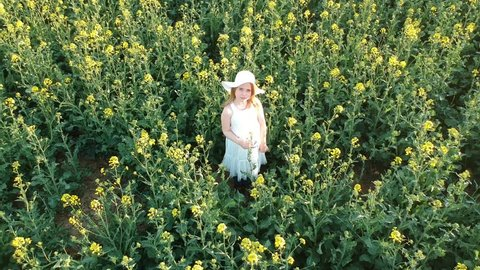 Aerial - Flying around little girl in white dress and hat in rape field