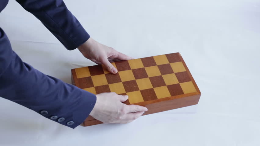 The hand puts the chess box on the table and opens it.   Shutterstock HD Video #1029121571