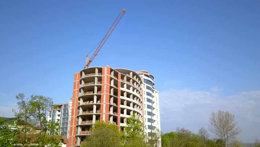 High industrial tower crane at construction site of new residential building.