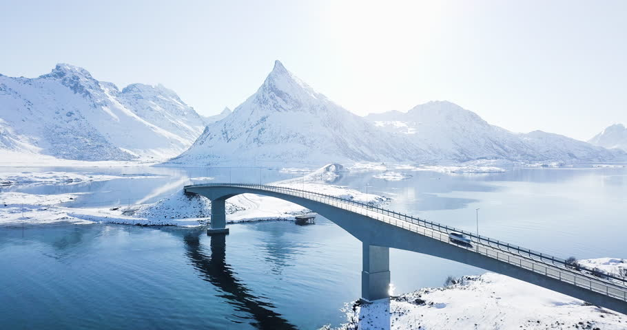 Scenic aerial footage of beautiful arctic Lofoten Islands winter wonderland scenery with car passing bridge on a sunny cold day, Fredvang, Lofoten archipelago, Norway, Scandinavia, northern Europe