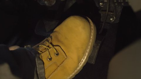 Big tan boot of male switching foot from brake to gas pedal at night in the  dark 4k driving
