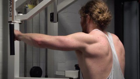 Young bearded ginger male training rear (back) shoulders hard on a pec deck in an old, rusty Arnold era gym (Gold's Gym) close-up
