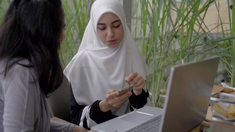muslim woman and friend discussing with laptop. student learning in cafe