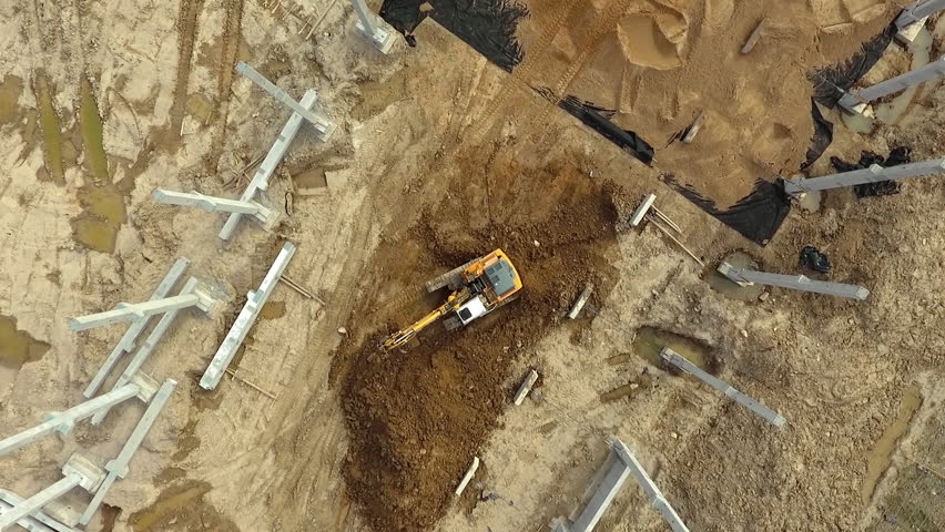 Aerial flight over new constructions site development where heavy machinery and construction workers are working with power tools in Eastern Europe, Lithuania, Alytus city outskirts. During cloudy day | Shutterstock HD Video #1029209681