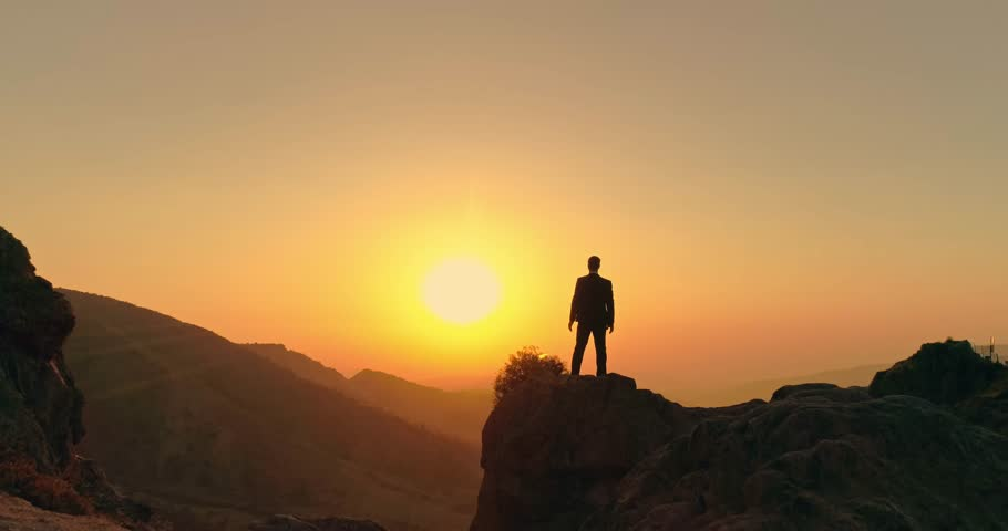 successful businessman standing on top of a mountain, victoriously raising his hands up - way to success, on top of world concept 4k aerial