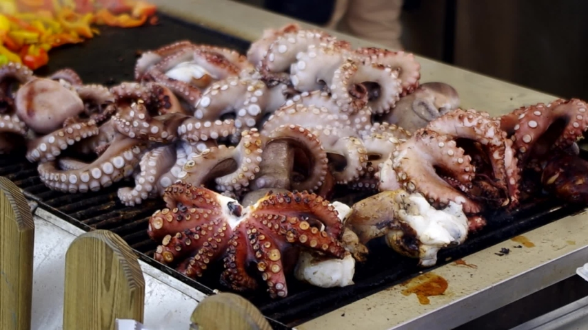 Octopus cooking on the grill during a street food festival.   Shutterstock HD Video #1029234311