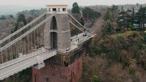 Backwards tracking shot reveal of the Clifton suspension bridge from right to left over the River Avon, Bristol, during overcast cloudy day. Filmed on DJI Mavic 2 Pro