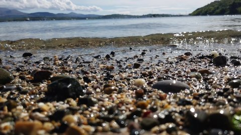 A low shot on the beach as the clear water of the sea gently rolls back and forth over the sand and pebbles.