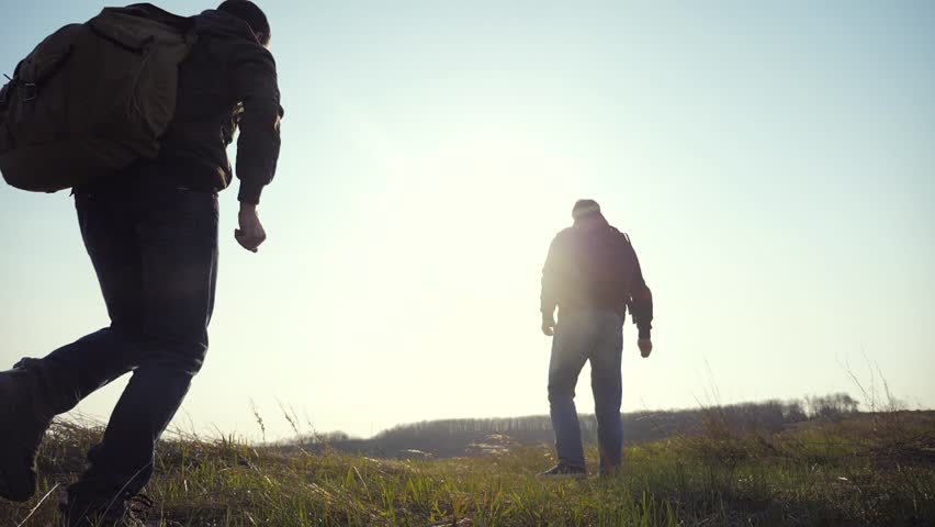 Teamwork help business travel silhouette concept. group hikers of people slow motion video walking in a field on trekking trip. tourists with backpacks traveling. happy family teamwork travel tourism | Shutterstock HD Video #1029308681