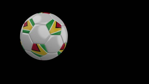 Soccer ball with the flag of Guyana flies past the camera, slow motion, 4k footage with alpha channel