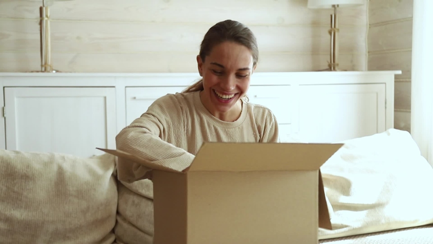 Excited young woman consumer open cardboard box get postal parcel, happy female customer receive carton package with gift sit on sofa at home satisfied with fast shipment online purchase delivery
