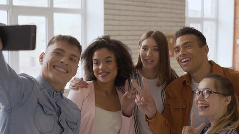 Say hello! mixed race group of 5 people. Cheerful people talking on a cell phone camera. teens laugh and say hi to the camera. virtual communication on the melt 4K