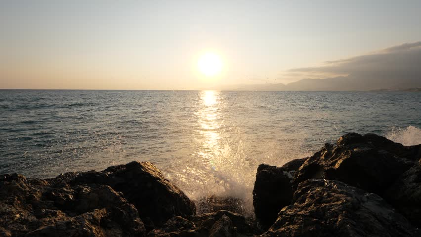 Wave move towards shore and splash on rough stones of breakwater, slow motion shot. Sunny morning time at north coast of Crete Island | Shutterstock HD Video #1029364181