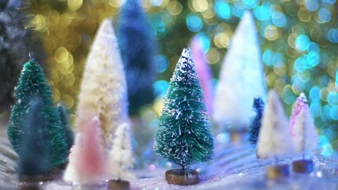 Slow motion snow glitter drops on retro bottle brush tree forest with blue and gold bokeh. A great background for a holiday greeting