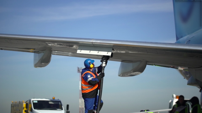 Airport airplane crew refueling aircraft on airline by technical staff maintenance ground. Preparing airplane for departure. service worker using fuel hose on aircraft wing, jet aviation fuel kerosene | Shutterstock HD Video #1029508841