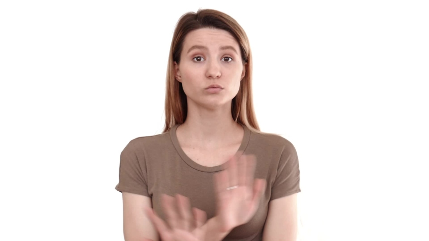 Portrait of a young pretty girl on a white background. A young girl says no and shows a stop sign with her hands. The girl refuses an offer. Confident girl. | Shutterstock HD Video #1029541001