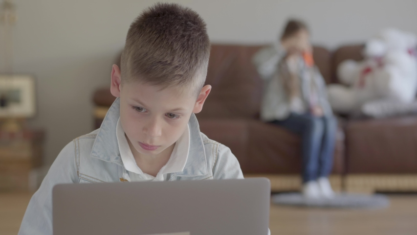 Small boy sit on the laptop computer and small girl, his twin sister blow soap bubbles on the sofa at home | Shutterstock HD Video #1029548591