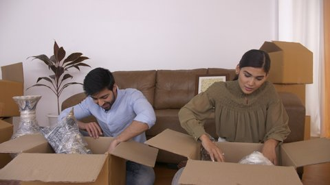 Attractive Indian Couple unpacking house - Moving cartons. Taking out books, home interiors, show piece. 4K Stock Footage of an Indian couple opening up carton boxes to move stuff to the new apartm...