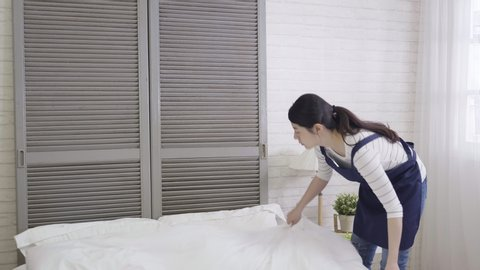 slow motion young female japanese housekeeper cleaning nightstand in hotel room. elegant asian wife in apron dress using duster on lamp on beside table moving alarm clock making up bed in apartment