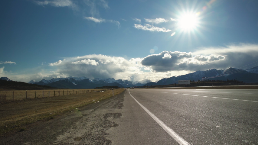 Wide angle of vehicles driving down highway with beautiful mountains and clouds in the background as the sun shines overhead #1029662771