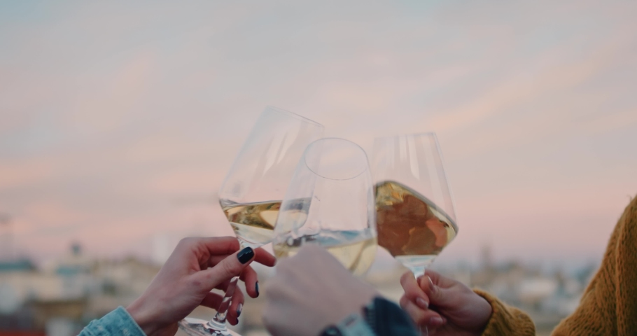 Hands cheering with glasses of white wine during the golden hour. With an old evening cityscape on their background. Slow Motion. Shot on RED digital cinema camera | Shutterstock HD Video #1029670811