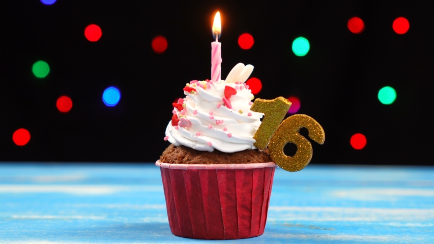 Delicious birthday cupcake with burning candle and number 16 on multicolored blurred lights background.