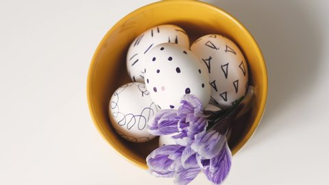 Woman moves yellow cup on a white background with Easter eggs. easter eggs in a yellow cup. white eggs with black pattern. beautiful filet flower on Easter eggs.