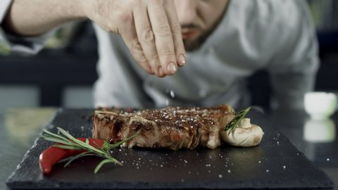 Chef salt grilled meat at stone cutting board. Closeup man hands salting steak in slow motion. Close up hands finishing ready steak. Closeup grill meat dish with vegetables at professional kitchen.