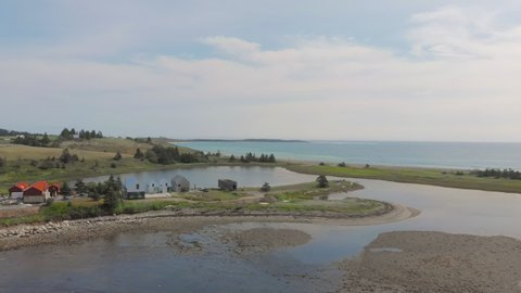 Cinematic drone / aerial static footage showing the ocean and a few chalets in Kingsburg, Nova Scotia, Canada during summer season.
