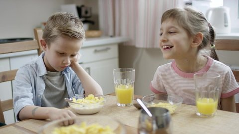 boy dont want to eat his cornflakes but mother makes him, and he laughed by his sister
