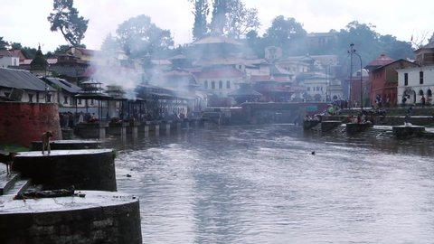 Extreme wide shot of Bagmati River with smoke rising from ritual cremations along the river near Pashupatinath Temple.