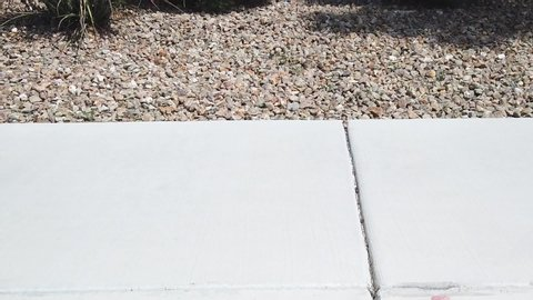Static, slow motion shot of a males feet, with flip flops, walking into the frame, on white concrete, gravel in the background, on a sunny day, in California, USA