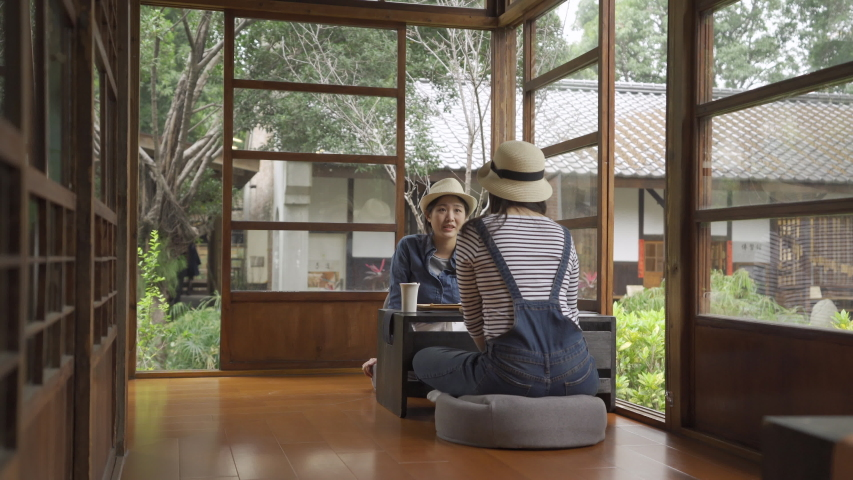 Back view of asian woman traveler with overalls sitting on wooden floor in japanese traditional house talking to friend in local restaurant. two female resting travel in kyoto japan do chado ceremony | Shutterstock HD Video #1029887441
