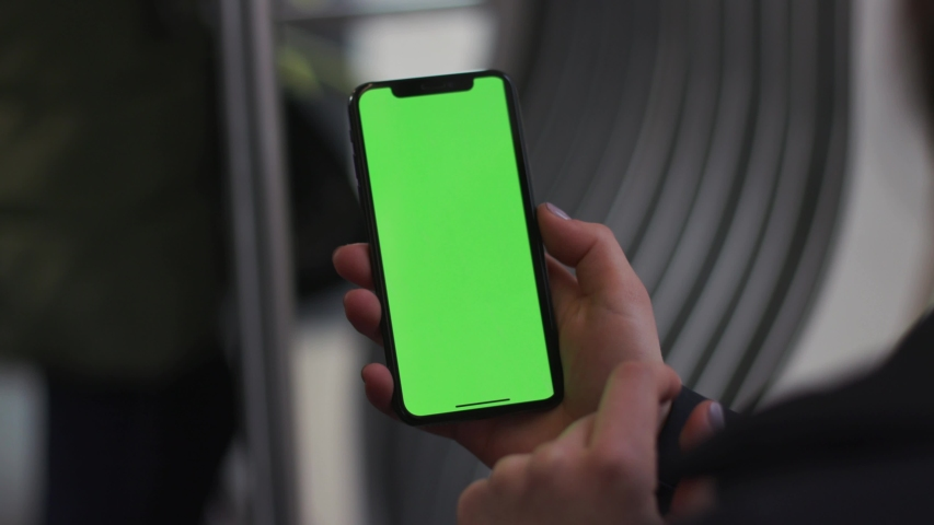 NEW YORK - 5 April 2018: Slow motion woman hands use touch holding a mobile telephone with a vertical green screen in tram chroma key smartphone technology cell phone street touch message display | Shutterstock HD Video #1029912311